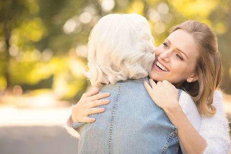 Smiling young woman hugging old mother in the park Stockfoto