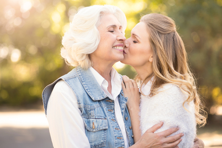 Involved woman kissing elderly mother in the park Stock Photo