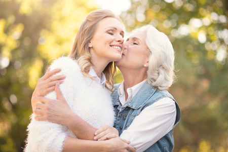 Aging mother kissing loving daughter in the park Stock Photo