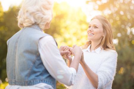 Kind woman holding hands with grandmother in the park Stock Photo