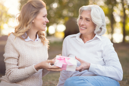 Creative mother congratulating mature daughter at the picnic Stock Photo