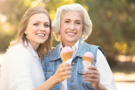 Happy young woman enjoying ice cream with old mother outdoors Stock Photo