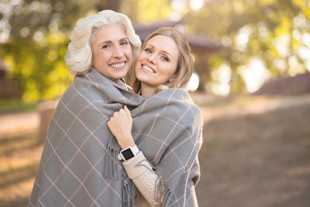 Joyful woman hugging retired mother at the picnic