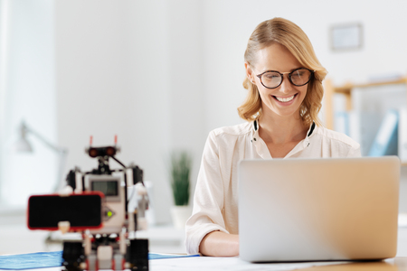 Charming businesswoman enjoying cooperation with robot indoors