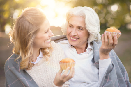 gerontology: Smiling woman spending picnic with old mother outdoors Stock Photo