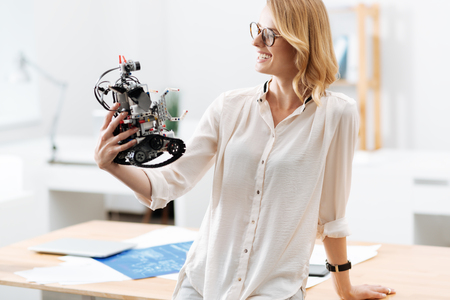 Smart engineer enjoying electronic robot functions in the laboratory
