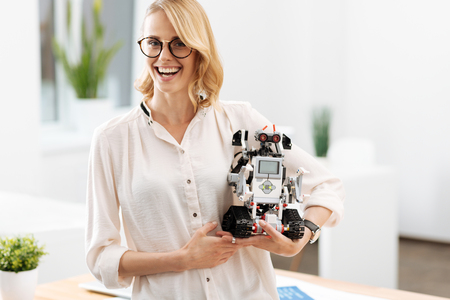 Delightful woman holding automatic little robot indoors Stock Photo