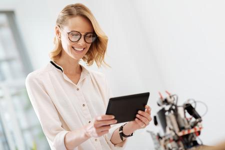 Blije vrouw die innovatieve gadgets in het bureau gebruiken