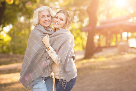 Upbeat woman hugging aged mother in the park Stock Photo