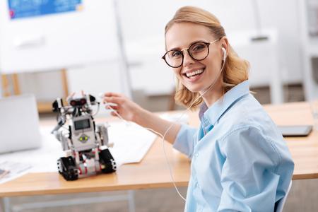 Charismatic woman enjoying music with electronic robot indoors Stock Photo