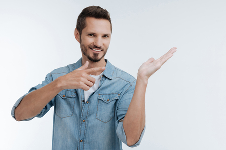 Cheerful smart man pointing at his left hand Stock Photo