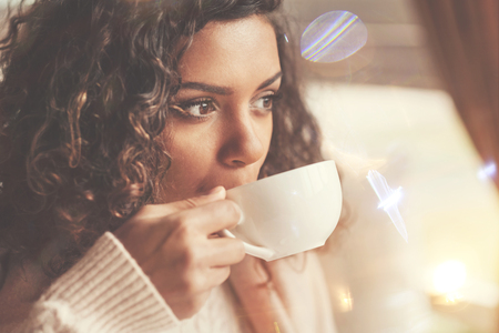 Mooie afro Amerikaanse vrouw die een slokje van thee neemt