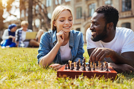 Positive pretty woman teaching her friend playing chess