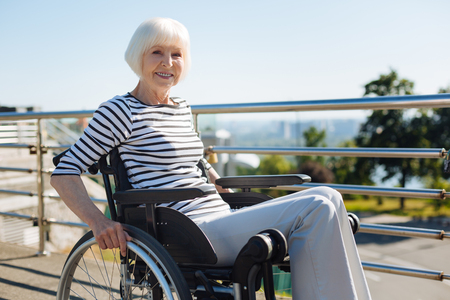 Inspiring lively woman wheeling the chair