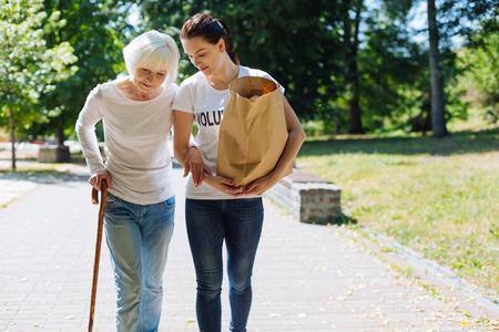 Unglaubliche Frau, die ältere Dame mit ihrer alltäglichen Routine unterstützt