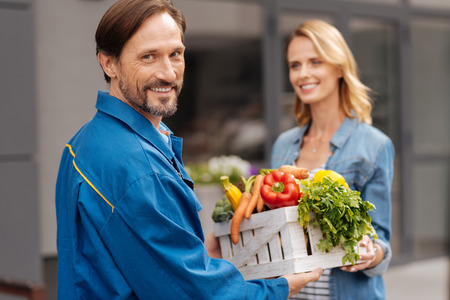Bright polite gentleman fetching goods for people Stock Photo