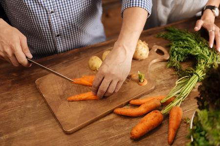 Lively clever man cooking vegetables for dinner