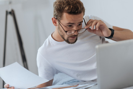 Confused young man touching his glasses