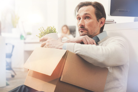 Sad employee looking at the office for the last time Stock Photo