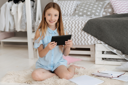 Charming girl smiling for camera while using digital tablet