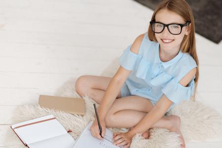 Charming smart girl smiling while preparing homework