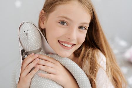 Joyful little girl posing with handmade toy