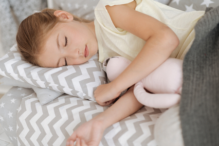 upbringing: Blonde little girl sleeping with her toy Stock Photo