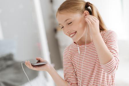 Young lady enjoying music in earphones