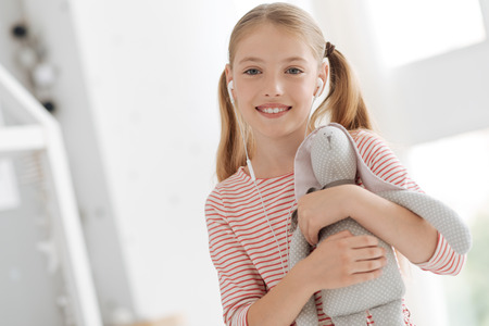 upbringing: Cheerful girl with earphones embracing bunny toy