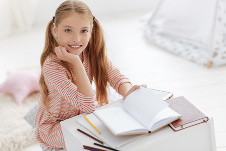 upbringing: Pretty female youngster smiling into camera while studying