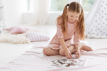 Well mannered kid playing puzzle game