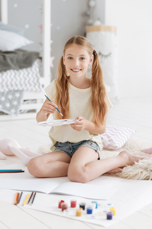 Smiling girl holding palette and smiling into camera Stock Photo