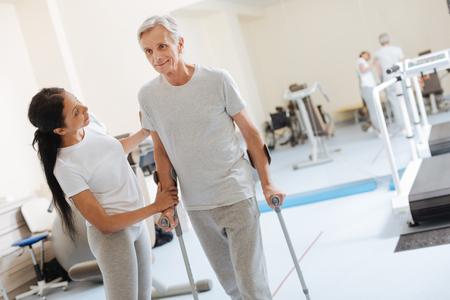 Smiling senior man leaning on walking sticks