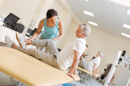 Pretty trainer explaining task for stretching leg