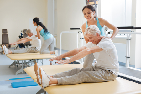 Positive delighted retirement doing stretching exercises Stock Photo