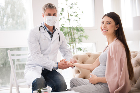 Delighted pregnant woman posing on camera