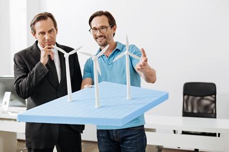 보스에 풍력 발전소 모델을 보여주는 유쾌한 엔지니어