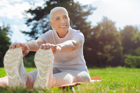 Joyful mature woman stretching her back Stock Photo