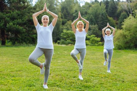 Three women standing on one leg