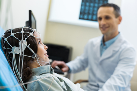 Medical specialist carrying out electroencephalographic diagnostics of patient Banque d'images