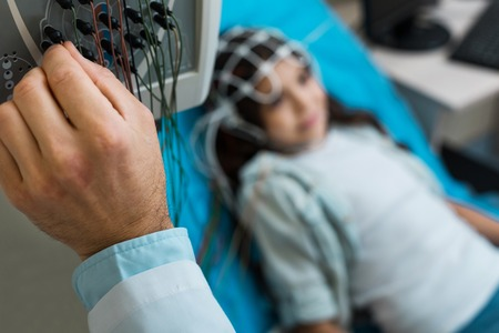 Close up of doctors hand setting up electroencephalograph Stock Photo