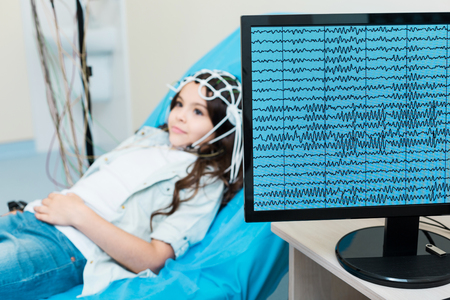 Little girl having her brain waves recorded via electroencephalograph 스톡 콘텐츠