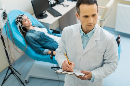Pleasant young doctor making notes about patients condition