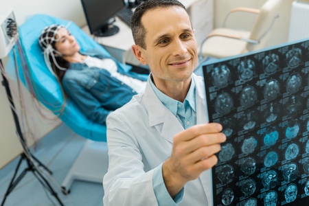 Pleasant doctor being pleased by CT results of his patient