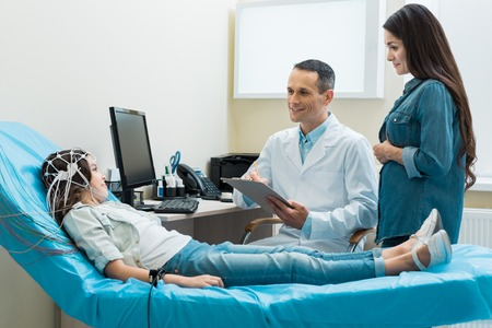 Doctor putting down answers of girl undergoing encephalography Stock Photo