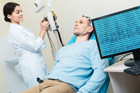 Young man having his brain waves recorded during electroencephalography Stock Photo