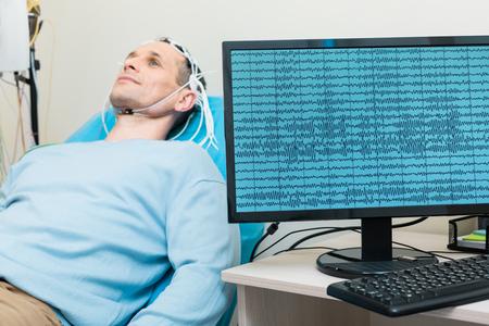 Gehirnwellen des jungen Mannes werden auf dem Bildschirm angezeigt Standard-Bild - 83991918