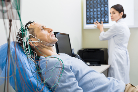 Female doctor carrying out electroencephalography of man