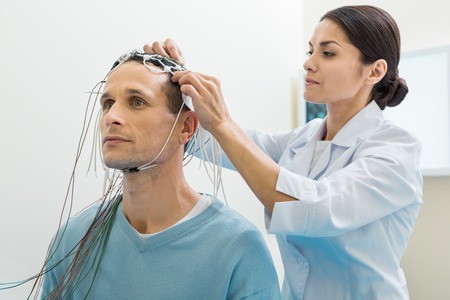 Female doctor putting electrodes on patients head Stock Photo