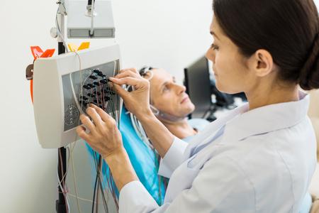 Female doctor tuning modern electroencephalograph 스톡 콘텐츠